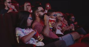 Family eating popcorn in cinema stock footage