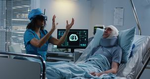 Doctor using VR headset during discussing diagnosis. Medium shot of a female doctor using VR headset during discussing diagnosis with elderly male patient stock photo