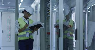 Female electrical worker reading paperwork. Medium shot of a female electrical worker reading paperwork and inspecting equipment in the control room of an stock image