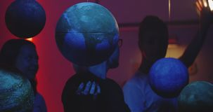 Young teacher teaching astronomy with planet models. Medium shot of a female teacher explaining astronomy to students with suspended planet models stock video footage