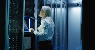 Female technician works on a tablet in a data center. Medium shot of female technician working on a tablet in a data center full of rack servers running royalty free stock photography