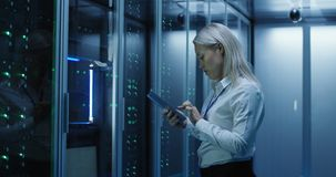 Female technician works on a tablet in a data center. Medium shot of female technician working on a tablet in a data center full of rack servers running royalty free stock image