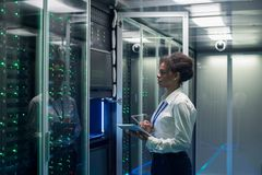 Female technician works on a tablet in a data center. Medium shot of female technician working on a tablet in a data center full of rack servers running royalty free stock images