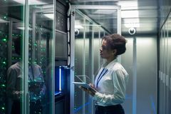 Female technician works on a tablet in a data center. Medium shot of female technician working on a tablet in a data center full of rack servers running stock photography