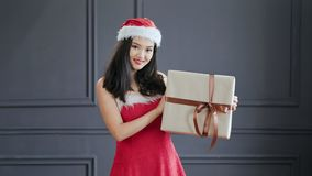 Medium shot festive Asian female wearing Santa Claus suit smiling and holding present at studio. Medium shot portrait of festive Asian female wearing Santa Claus