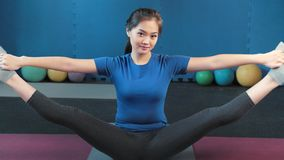 Medium shot friendly Asian sportswoman showing perfect stretching professional yoga or pilates woman. Medium shot friendly Asian sportswoman showing perfect stock footage