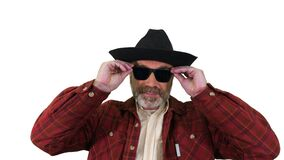 Ranger in a cowboy hat putting on sunglasses and smiling to camera on white background.