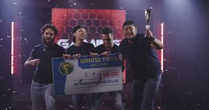Gaming tournament team celebrating their victory. Medium shot of a gaming tournament team holding their prize while celebrating their victory stock video