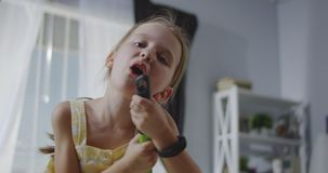 Girl singing with broom handle stock video