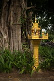 Medium shot of a gold spirit house and large tree in Southeast Asia Stock Photos