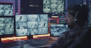 Hacker watching security camera footage. Medium shot of a hacker watching hacked security camera footage stock footage