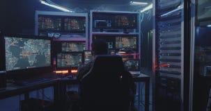 Hacker watching multiple monitors. Medium shot of a hacker watching multiple monitors while working stock footage