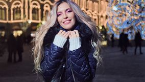 Charming female at Christmas evening outdoor smiling at illumination bokeh decoration background. Medium shot happy charming female having good time outdoor at stock video footage
