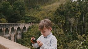 Medium shot happy cute little European boy taking smartphone photo at Ella Nine Arches Bridge on Sri Lanka vacation. Cheerful carefree smart 4-6 year old child stock video