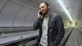 Happy man making a call on escalator. Medium shot.Happy man making a call on escalator. Professional shot in 4K resolution. 02. You can use it e.g. in your stock video