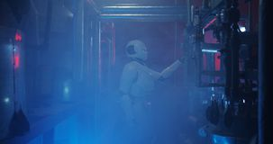 Humanoid robot working in a smoke filled lab. Medium shot of a humanoid robot checking a gauge in a smoke filled lab stock photo