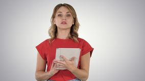 Lady wearing red t-shirt holding a tablet in her hands with a serious face talking to camera on gradient background. stock photos