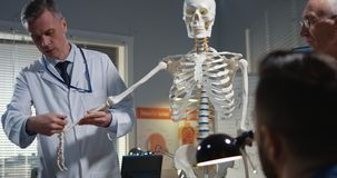 Doctor explaining diagnosis to his colleagues. Medium shot of a male doctor explaining diagnosis to his colleagues with a cervical spine x-ray and a skeleton royalty free stock photography