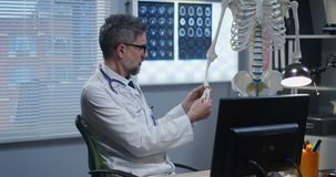 Doctor using skeleton model for analyzing hand anatomy. Medium shot of male doctor using a skeleton model for analyzing hand anatomy stock footage