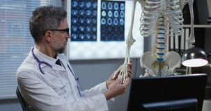 Doctor using skeleton model for analyzing hand anatomy. Medium shot of male doctor using a skeleton model for analyzing hand anatomy stock video footage