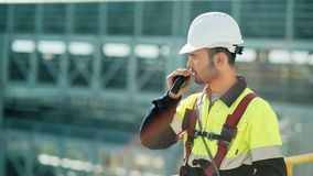 Medium shot of male professional engineer wearing hard hat talking using walkie talkie