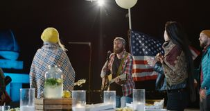Male singer in a plaid shirt with his bassist. Medium shot of male singer in a plaid shirt with his bassist singing and playing guitar on a urban rooftop at stock video