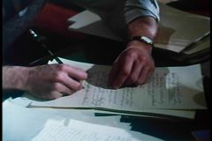 Medium shot of man briskly writing on paper with pencil stock video
