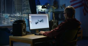 Man designing hinge on a computer. Medium shot of a man using a computer to design a hinge at home stock video footage