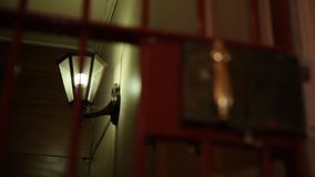 Metal door with lamp. A medium shot of a metal door with a lamp at the background stock footage