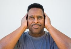 Medium shot of a middle aged black man with hands covering his ears stock photos