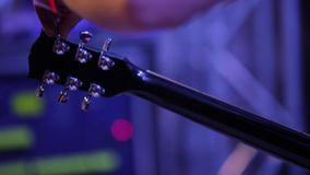 Medium shot of musician's arm tuning electric guitar backstage at concert stock footage
