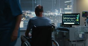 Nurse pushing wheelchaired patient to a window. Medium shot of a nurse pushing and elderly male patient to a window in a wheelchair stock footage