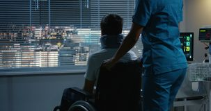 Nurse pushing wheelchaired patient to a window. Medium shot of a nurse pushing teenage male patient to a window in a wheelchair stock video
