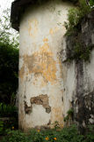 Medium shot of old corner guard tower at colonial era prison in. Southeast Asia. White curved stucco surface is shipped and faded, with vegetation below and Royalty Free Stock Photo