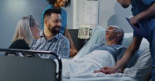 Patient lying in hospital among visitors stock photos