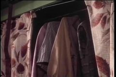 Medium shot of person removing clothes from closet stock footage