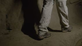 Person walking on tunnel. A medium shot of a person walking on a tunnel holding a flash light stock footage