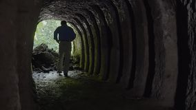 Person walking on tunnel. A medium shot of a person walking on a tunnel holding a flash light stock video footage