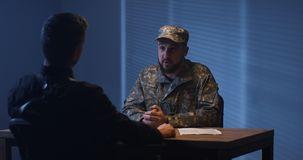 Policeman interrogating a soldier stock images