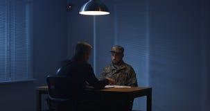 Policeman interrogating a soldier. Medium shot of a policeman interrogating a soldier royalty free stock photo