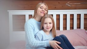 Medium shot portrait of happy mother hugging her little daughter looking at camera stock footage