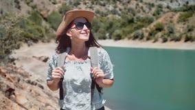 Medium shot portrait hiker woman ascending on mountain enjoying amazing seascape. Female backpacker in sunglasses and hat smiling admiring nature having good stock video footage