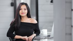 Portrait seductive Asian fashion girl wearing black dress sitting at working table stock video