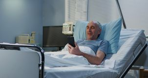 Male patient using video call in hospital room stock image