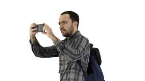Handsome young man carrying backpack and taking a picture of himself on white background. Medium shot side view. Handsome young man carrying backpack and taking royalty free stock photo