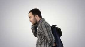 Portrait of man putting backpack on on gradient background. Medium shot side view. Portrait of man putting backpack on on gradient background. Professional shot stock video