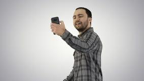 Teenage boy making a selfie when walking on gradient background. stock images