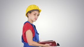 Woman construction worker in hard hat and workwear uniform checking the list on gradient background.