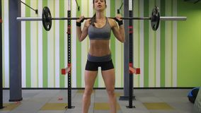 Medium shot slow mo tilt-down tilt-up men and women exercising and lifting weights female bodybuilder champion athlete. Doing power clean in cross fit gym stock footage
