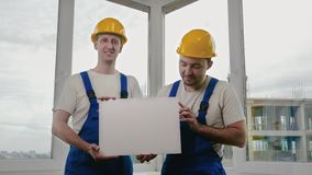 Smiling builders wearing hardhats showing blank board. Medium shot.Smiling builders wearing hardhats showing blank board. Professional shot in 4K resolution stock video